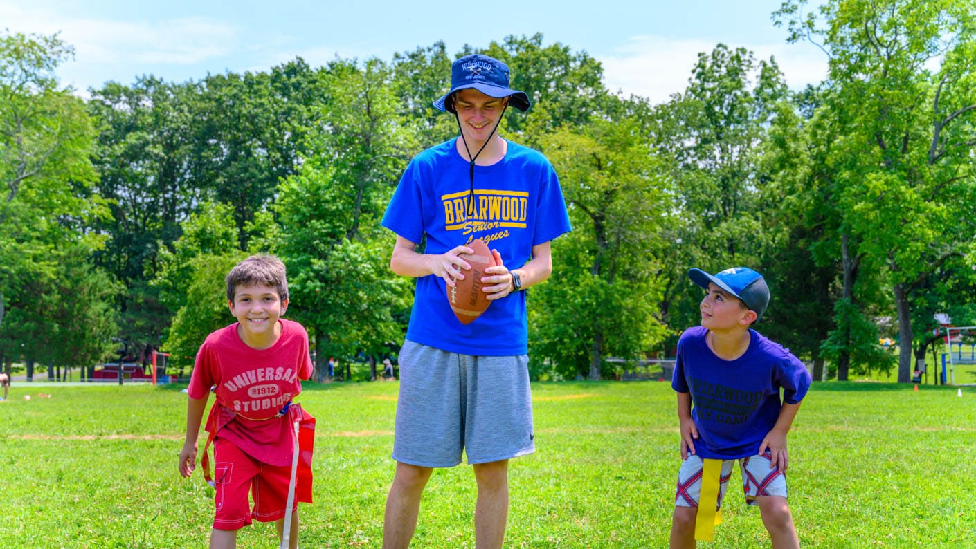 Counselor with boys playing football
