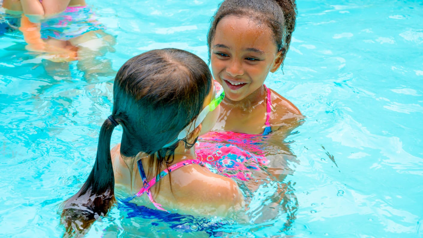 Two girls swimming and laughing in pool